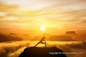 Woman standing in yoga position, meditating in mountains